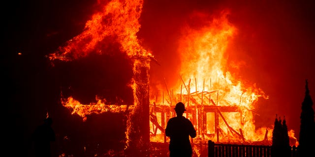 A home burns as the Camp Fire rages through Paradise, Calif,. onNov. 8, 2018. (AP Photo/Noah Berger,File)
