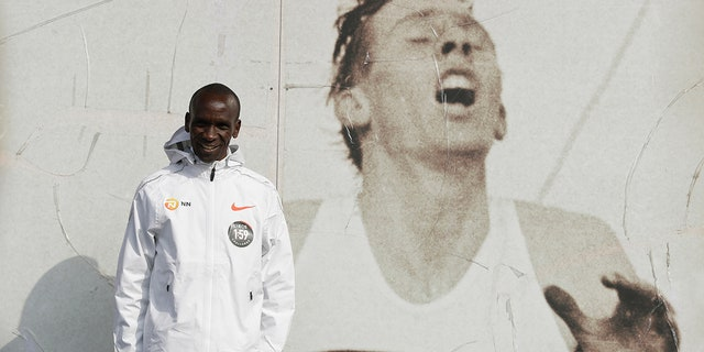 Marathon world record holder Kenya's Eliud Kipchoge poses for photographers next to an image of British athlete Roger Bannister, who in 1954 ran to become the first person ever to break the four-minute mile barrier, at the Iffley Road Track, in Oxford, England, Tuesday, April 30, 2019. (AP Photo/Matt Dunham)