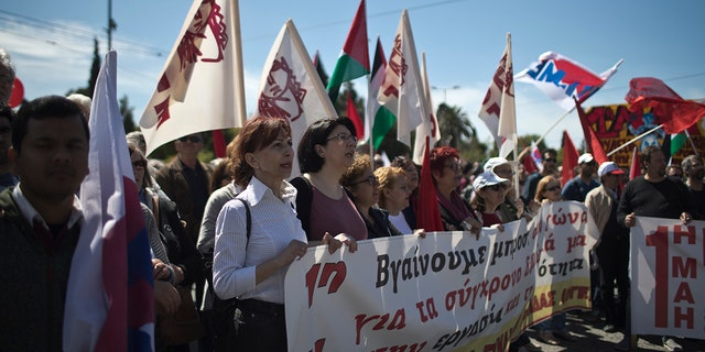 Protesters sing slogans during a rally by the Communist-affiliated PAME union outside the Greek parliament in central Athens.