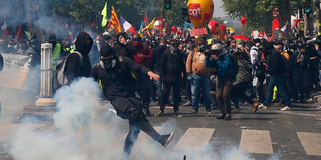 An activist kicks away a tear gas canister during a May Day demonstration in Paris. (AP Photo/Francois Mori)