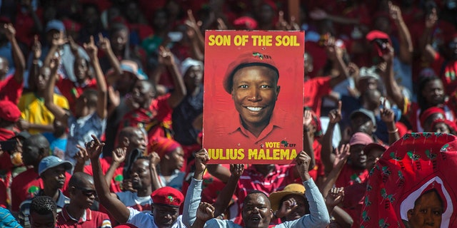 Supporters of the Economic Freedom Fighters (EFF) party, hold up an election poster of leader Julius Malema during a May Day Rally in Alexandra Township, Johannesburg, Wednesday, May 1, 2019. (AP Photo/Mujahid Safodien)