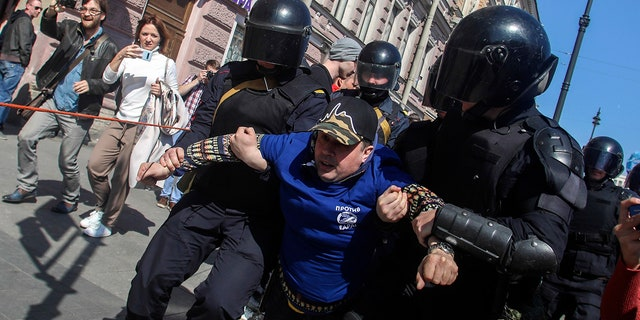 Riot police officers detain protesters during a rally in St. Petersburg, Russia, Wednesday, May 1, 2019.