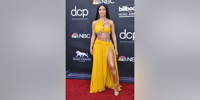 Cardi B rocks a yellow two piece outfit with jewel detailing.