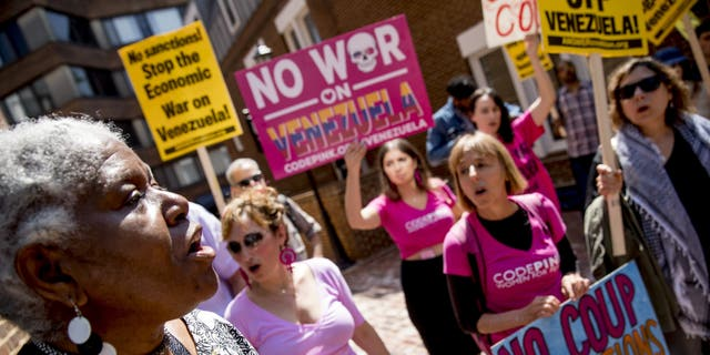 U.S. activist Medea Benjamin, co-founder of the anti-war group Code Pink, second from right, and others, sing together outside the Venezuelan Embassy in Washington, Thursday, May 2, 2019.  (AP Photo/Andrew Harnik)