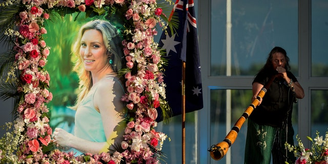 """FILE - In this Aug. 11, 2017, file photo, Johanna Morrow plays the didgeridoo during a memorial service for Justine Ruszczyk Damond at Lake Harriet in Minneapolis. The city of Minneapolis is paying $20 million to settle a lawsuit over former police officer Mohamed Noor's fatal shooting of the unarmed Damond who approached his squad car after calling 911 to report a possible crime. Mayor Jacob Frey announced the settlement Friday, May 3, 2019, three days after a jury convicted Noor of murder and manslaughter in the 2017 death of Damond. Frey called the settlement """"a way for our city to move forward."""""""