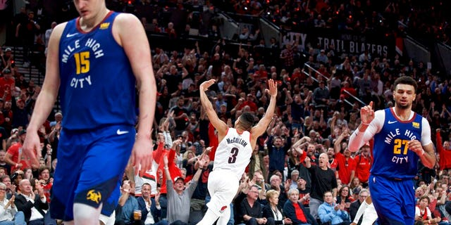 Portland Trail Blazers guard CJ McCollum, center, reacts after making a three point basket against the Denver Nuggets during overtime of Game 3 of an NBA basketball second-round playoff series Friday, May 3, 2019, in Portland, Ore.