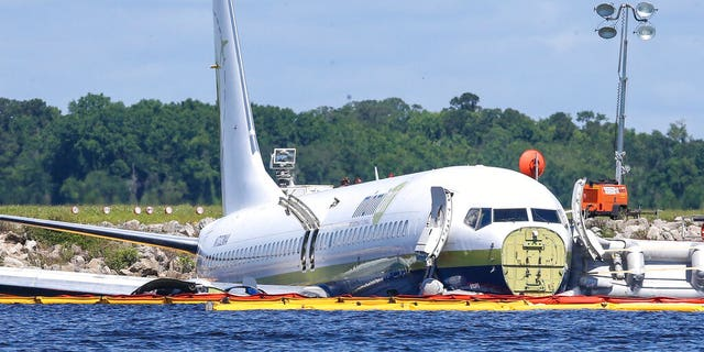 A charter plane carrying 143 people and traveling from Cuba to north Florida sits in a river at the end of a runway, Saturday, May 4, 2019 in Jacksonville, Fla.