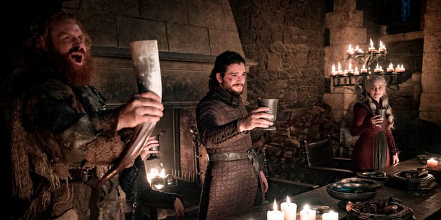 This image released by HBO shows Kristofer Hivju, from left, Kit Harington and Emilia Clarke in a scene from 'Game of Thrones.' Fans got a taste of the modern world when eagle-eyed viewers spotted a takeout coffee cup on the table during a celebration in which the actors drank from goblets and horns.