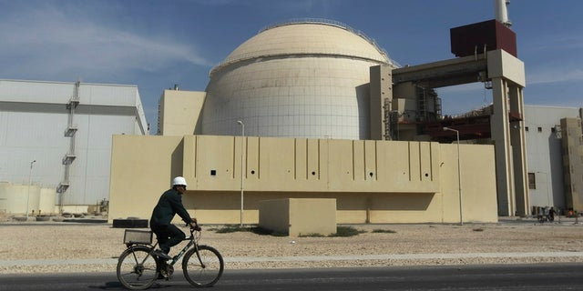 A worker rides a bike in front of the reactor building of the Bushehr nuclear power plant, outside Bushehr, Iran. (Associated Press)