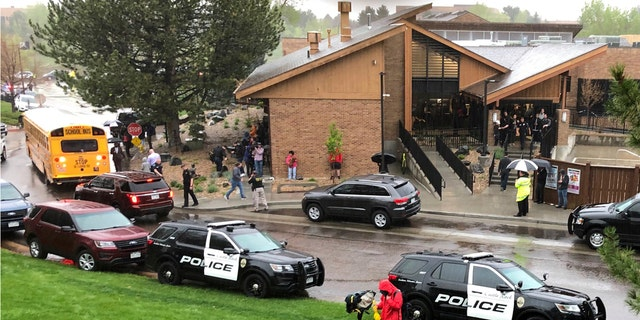 Police and others are seen outside a recreation center where students are reunited with their parents, in the Denver suburb of Highlands Ranch, Colo., after a shooting at STEM School Highlands Ranch on Tuesday.