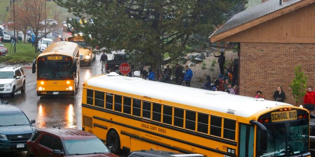 School buses arrive at a recreation center set up for students to get reunited with their parents after a shooting at a suburban Denver middle school. (Associated Press)