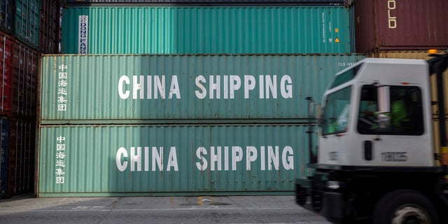 A jockey truck passes a stack of 40-foot China Shipping containers at the Port of Savannah in Savannah, Ga. For months, the U.S. economy has shrugged off the tariffs slapped by America and China on tens of billions of dollars of each other's goods. (Associated Press)