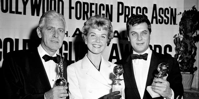 In this Feb. 26, 1958 file photo, actress Doris Day, center, Tony Curtis, right, and Buddy Adler pose with their awards presented to them by the Hollywood Foreign Press Association at its annual awards dinner in the Cocoanut Grove in Los Angeles. — AP