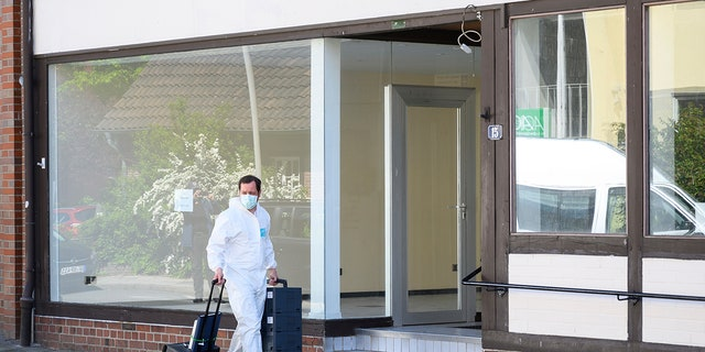 A crime scene officer arrives a crime scene where the bodies of two women have been found at an apartment in Wittingen, northern Germany, Monday, May 13, 2019. The women found dead in an apartment of one of three people who found dead on Saturday at a hotel in Passau, several hundred kilometers away in a mysterious case involving crossbows. (Christophe Gateau/dpa via AP)