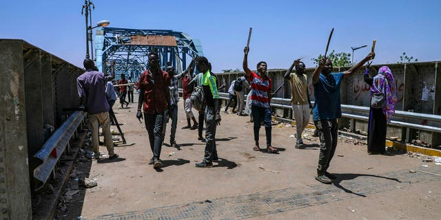 Protesters walk towards the sit-in protest outside the Sudanese military headquarters, in Khartoum, Sudan, Tuesday, May 14, 2019.