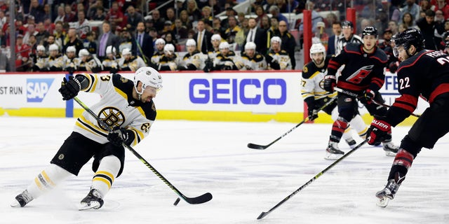 Boston Bruins' Brad Marchand (63) controls the puck against Carolina Hurricanes' Brett Pesce (22) during the first period in Game 3 of the NHL hockey Stanley Cup Eastern Conference final series in Raleigh, N.C., Tuesday, May 14, 2019. (Associated Press)