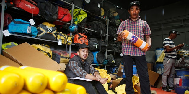Record-holding Sherpa guide Kami Rita checks oxygen cylinders and other supplies needed for climbing Mount Everest, in Kathmandu, Nepal. (AP Photo/Niranjan Shrestha, File)