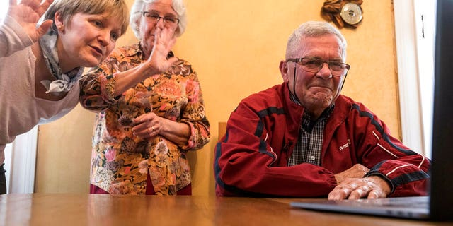 In this photo taken May 8, 2019, Andre Gantois, his wife Rosine, center, and daughter Isabelle talk to his half-brother Allen Henderson, of the U.S, during a video-conference call in Ludres, eastern France.