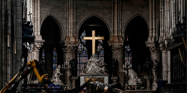 Rubble and the cross inside the Notre Dame de Paris Cathedral, Wednesday May 15, 2019 in Paris. French Culture Minister Franck Riester says that one month after a fire engulfed Notre Dame Cathedral, the edifice is still being made safe enough for restoration to begin. (Philippe Lopez/Pool via AP)