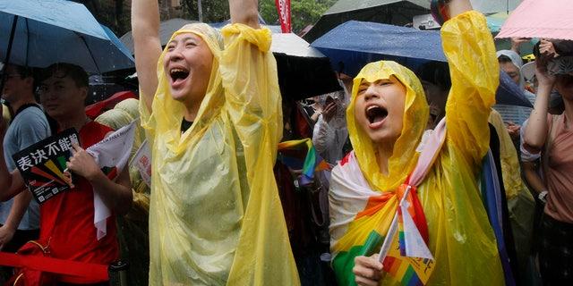 طرفداران ازدواج از همان جنس در روز جمعه، در مجلس قانونگذاری یوان در تایپه، تایوان، پس از تصویب قانون مجازات ازدواج همجنسگرایان برای اولین بار برای آسیا، تایید شده است. (اسوشیتد پرس)
