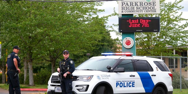 Police are positioned outside Parkrose High School during a lockdown after a man, said to be armed, was wrestled to the ground by a staff member on Friday. The Portland Police Bureau said in a statement Friday that no shots were fired and a suspect is in custody. (Dave Killen/The Oregonian via AP)