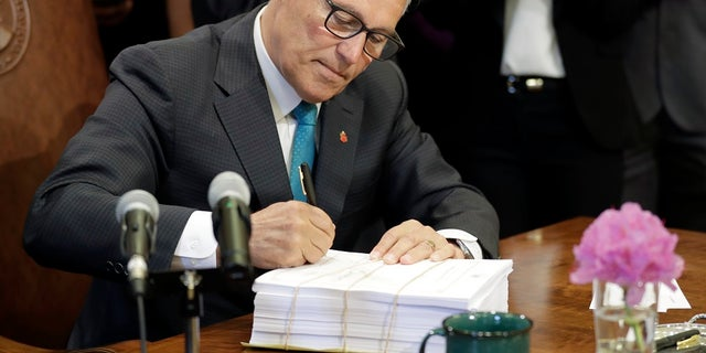 "Washington Gov. Jay Inslee signs the state operating budget, Tuesday, May 21, 2019, at the Capitol in Olympia, Wash. Inslee also signed a ""sanctuary state"" measure on Wednesday. (AP Photo/Ted S. Warren)"