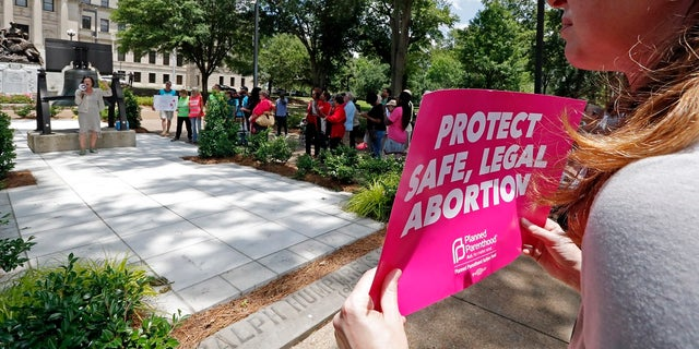 An abortion rights advocate holds signage at the Capitol in Jackson, Miss., voicing her opposition to state legislatures passing abortion bans that prohibit most abortions once a fetal heartbeat can be detected, Tuesday, May 21, 2019. The rally in Jackson was one of many around the country to protest abortion restrictions that states are enacting. (AP Photo/Rogelio V. Solis)