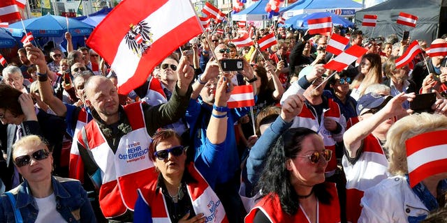 Supporters wave Austrian flags during the final election campaign event of the right-wing Freedom Party, FPOE, for European elections in Vienna, Austria, Friday, May 24, 2019.