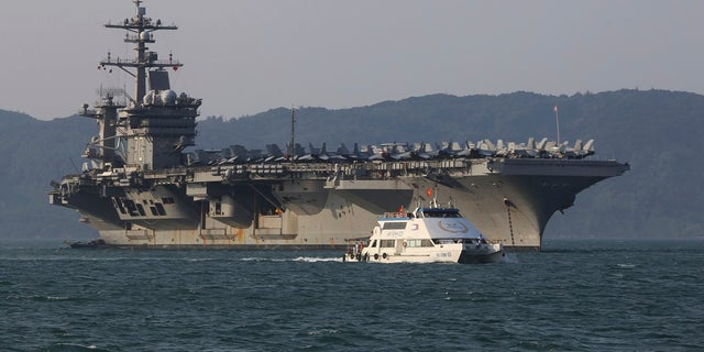 In this March 5, 2018, file photo, a Vietnamese passenger boat sails past U.S. aircraft carrier USS Carl Vinson as it docks in Danang bay, Vietnam. A U.S. sailor has pleaded guilty to espionage and sentenced to three years after admitting he took classified information about a Navy's nuclear-powered warship and planned to give it to a journalist and then defect to Russia officials said Friday, (AP Photo/Hau Dinh, File)