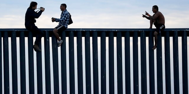 In this Nov. 21, 2018, file photo, two Honduran men pose as a photographer, at left, takes their picture after the group climbed the border wall separating Tijuana, Mexico, and San Diego, before climbing back down on the Mexican side, seen from San Diego. (AP Photo/Gregory Bull, File)