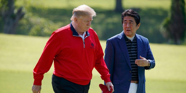 President Donald Trump walks with Japanese Prime Minister Shinzo Abe before playing a round of golf at Mobara Country Club, on Sunday, in Chiba, Japan. (Associated Press)