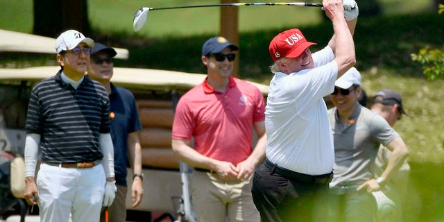 U.S. President Donald Trump, right, plays golf with Japanese Prime Minister Shinzo Abe, left, at Mobara Country Club in Mobara, south of Tokyo, on Sunday. (Associated Press)