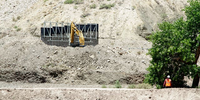 FILE: A construction worker watches a section of fencing be moved for a privately-funded border fence on private land in Sunland Park, New Mexico.