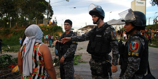 A woman asks police officers for further information outside the Anisio Jobim prison complex in Manaus, Amazonas state, Brazil, Monday, May 27, 2019. (AP Photo / Edmar Barros)