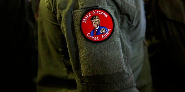 """A service member wears a patch that says """"Make Aircrew Great Again"""" as they listen to President Trump speak Tuesday aboard the USS Wasp in Japan. (Associated Press)"""