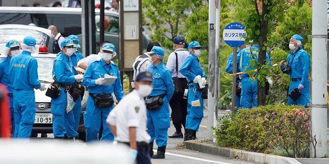 Investigators work near a bus stop for CARITAS Elementary School bus at the scene of an attack in Kawasaki, near Tokyo Tuesday, May 28, 2019. (Shigeyuki Inakuma/Kyodo News via AP)