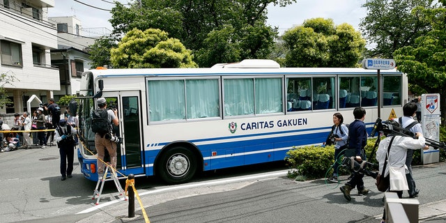 CARITAS Elementary School bus is seen near the scene where a man wielding a knife attacked commuters in Kawasaki, near Tokyo Tuesday, May 28, 2019.(Kyodo News via AP)