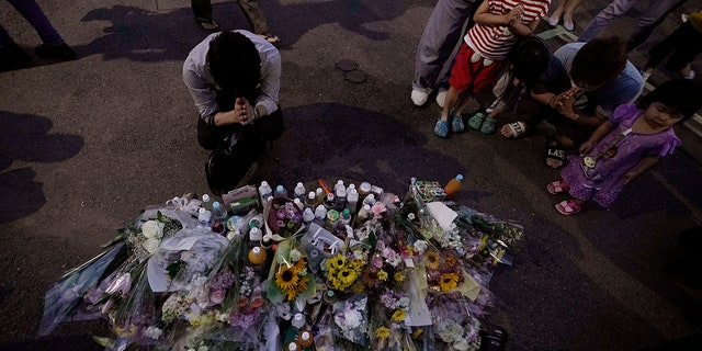 People pay their respects at a makeshift memorial for the victims of a knife attack Tuesday, May 28, 2019, in Kawasaki, just outside Tokyo. (AP Photo/Jae C. Hong)