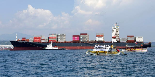 ​​​​​​​In this image released by Greenpeace, Greenpeace activists and other environmental organizations display a banner as the cargo ship MV Bavaria, the container vessel allegedly hired to ship back the 69 containers loaded with garbage from Canada, slowly enters the mouth of Subic Bay, Thursday, May 30, 2019 in Subic, Zambales province west of Manila, Philippines.