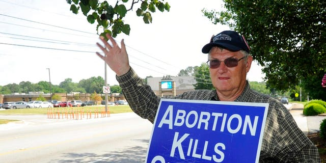 Jim Snively, of Huntsville, waves to passing cars while holding an anti-abortion sign in front of the Alabama Women's Wellness Center. (AP Photo/Eric Schultz)