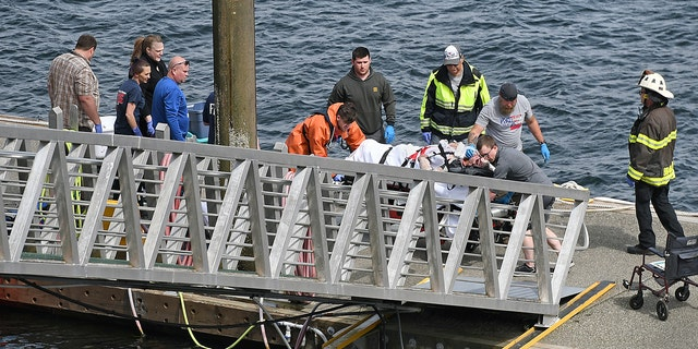 An injured passenger is helped to an ambulance after two floatplanes collided near Ketchikan, Alaska Monday afternoon. (Dustin Safranek/Ketchikan Daily News via AP)