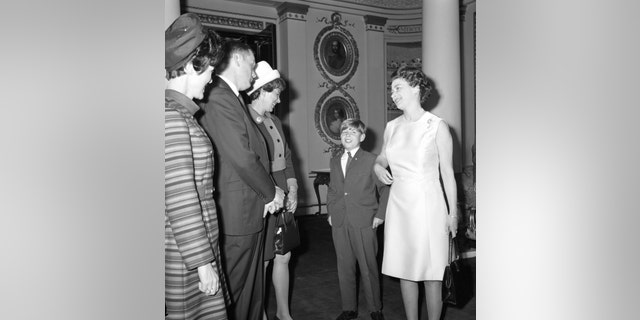 File photo - Queen Elizabeth II and Prince Andrew talk with Neil Armstrong, his wife Janet and Pat Collins, left, wife of Colonel Michael Collins, at Buckingham Palace. Janet Armstrong is wearing the lunar brooch on her lapel.