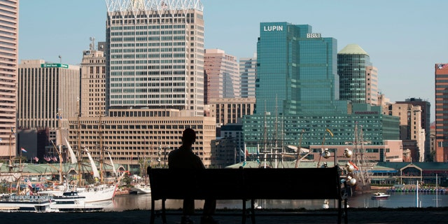 File photo - a man sits on a park bench overlooking Baltimore harbor and skyline, Baltimore, Maryland. (Photo By: Education Images/UIG via Getty Images)