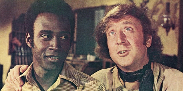 Actor Gene Wilder (right) puts his arm around the shoulder of Cleavon Little in a still from the film, 'Blazing Saddles,' directed by Mel Brooks, 1974. (Photo by Warner Bros./Courtesy of Getty Images)