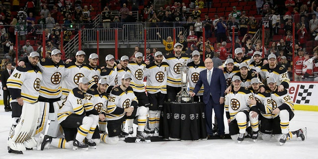 Players of the Boston Bruins post the Prince of Wales trophy and Bill Daly, deputy commissioner of the National Hockey League, following Game 4 of NHL hockey in Eastern Conference finals of the Stanley Cup against the Carolina Hurricanes in Raleigh, NC, on Thursday. Boston won 4-0 to advance to the Final Stanley Cup. (Associated Press)