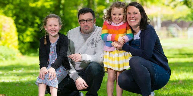 Rachel Avon, with her daughters Ffion (left) and Cari, and partner Ross, said she would have never known she had the rare cancer if her growing unborn baby wasn't pushing on the tumor to cause pain.