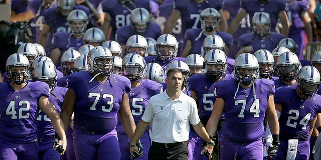 St. Thomas manager Glen Caruso leads his group onto a margin for a college football diversion opposite St. John's, in St. Paul, Minn. (Jim Gehrz/Star Tribune around AP)