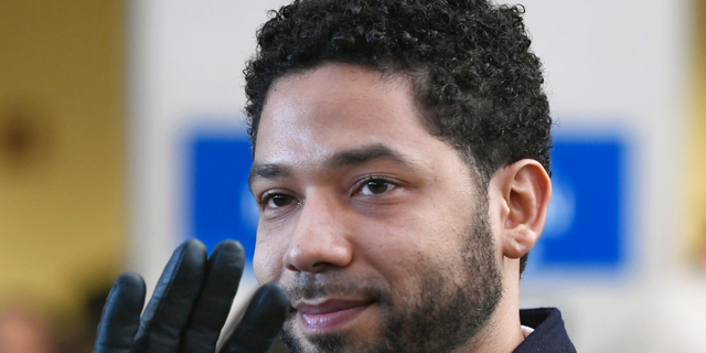 In this March 26, 2019 file photo, actor Jussie Smollett smiles and waves to supporters before leaving Cook County Court after his charges were dropped in Chicago.
