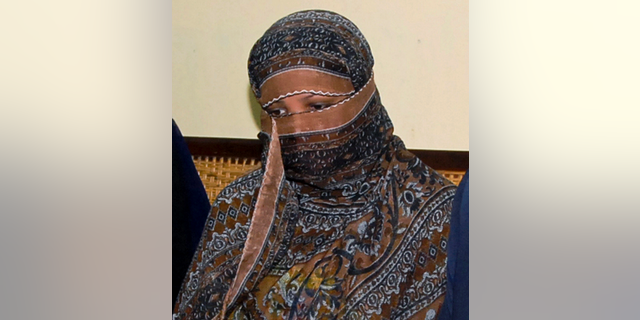 """FILE - In this Nov. 20, 2010, file photo, Aasia Bibi, a Pakistani Christian woman, listens to officials at a prison in Sheikhupura near Lahore, Pakistan.  Pakistani media say Aasia Bibi, a Christian woman acquitted of blasphemy after spending eight years on death row, has left Pakistan for Canada to be reunited with her daughters. Wilson Chawdhry of the British Pakistani Christian Association told The Associated Press on Wednesday, May 8, 2019, he received a telephone text message from a British diplomat stating simply that """"Aasia is out.""""  (AP Photo, File)"""