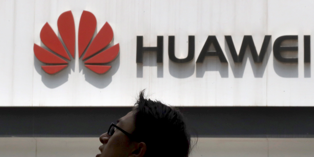 In this photo taken Thursday, May 16, 2019, a man walks past by a Huawei store in Beijing. (AP Photo/Ng Han Guan)